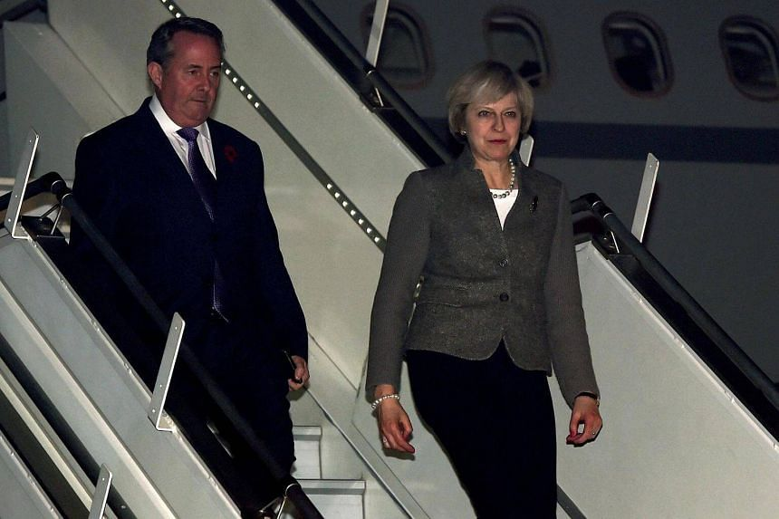 Britain's Prime Minister Theresa May looks on as she arrives at the airport in New Delhi on Nov 6, 2016.