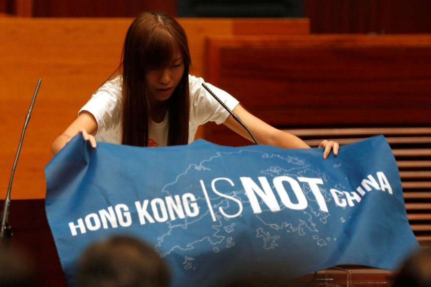 Newly elected lawmaker Yau Wai Ching displays a banner before taking the oath at the Legislative Council in Hong Kong on Oct 12, 2016.