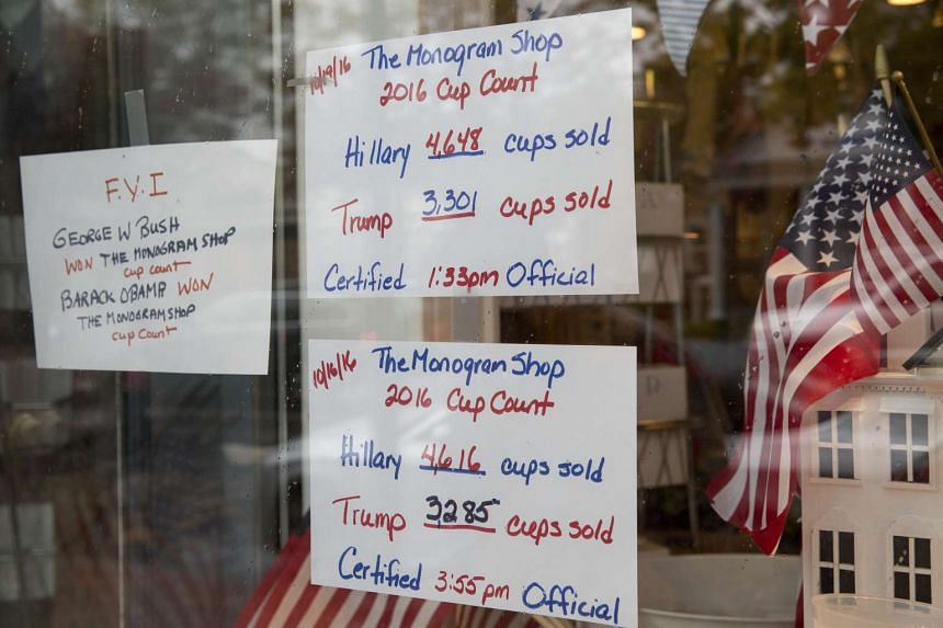 Signs in the window of Ms Valerie Smith's Monogram Shop updating her candidate cup sales in October. The number of cups sold has correctly predicted the last three races.