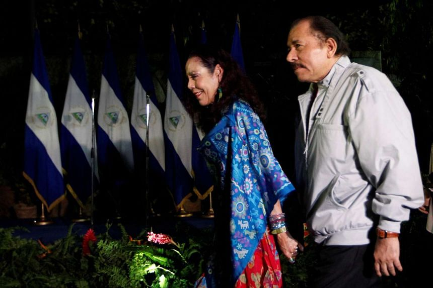 Daniel Ortega, Nicaragua's current president and presidential candidate from the ruling Sandinista National Liberation Front, holds hands with his wife and vice presidental candidate Rosario Murillo after casting their vote at a polling station durin