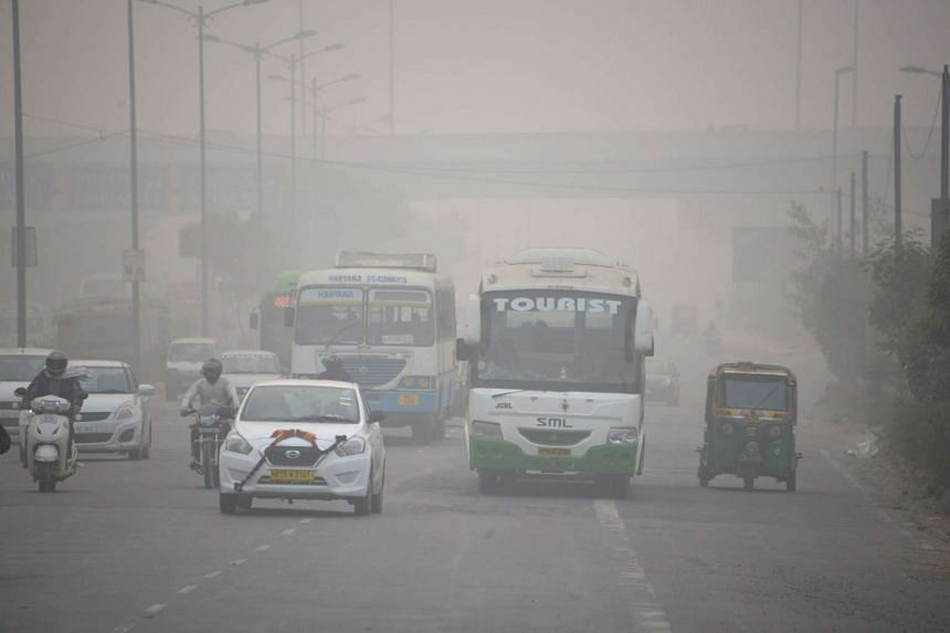 Indian commuters travel along a road under cover of heavy smog, in New Delhi on Nov 7, 2016.