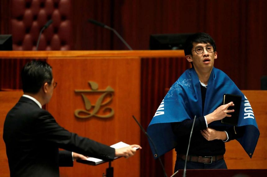 Newly elected lawmaker Baggio Leung wears a banner 'Hong Kong is not China' while taking the oath at the Legislative Council in Hong Kong on Oct 12, 2016.