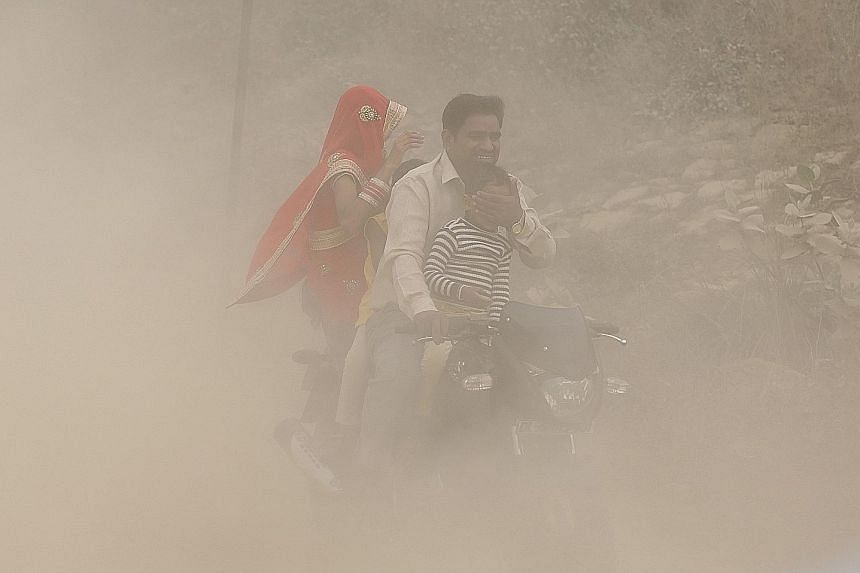 A family riding through the heavy pollution in New Delhi on Sunday, where the poor air has forced a million schoolchildren to stay at home. Mr K. K. Agarwal, president of the Indian Medical Association, has called the current haze blanketing the city