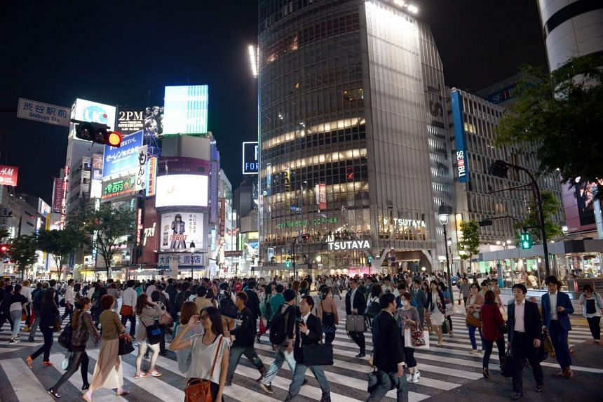 Pedestrians walking across the road at Shibuya's famous crossing.