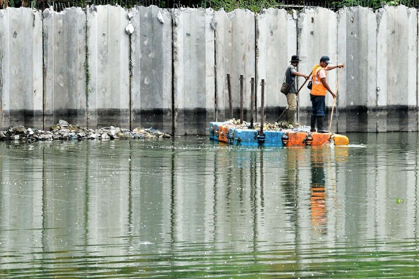 Workers clean the city water reservoir in Jakarta.