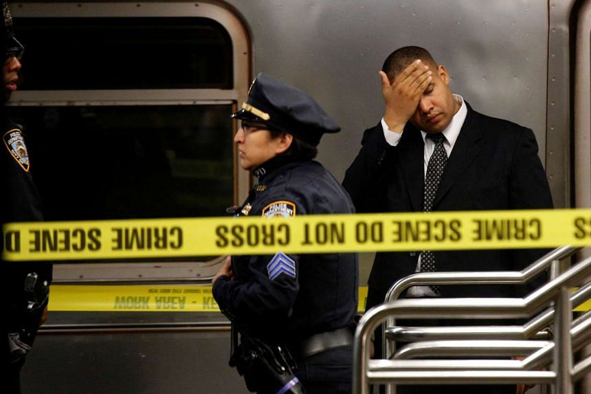 Members of the New York City police (NYPD) work at the scene after a commuter was pushed in front of a subway train as it arrived at Times Square station in New York City.