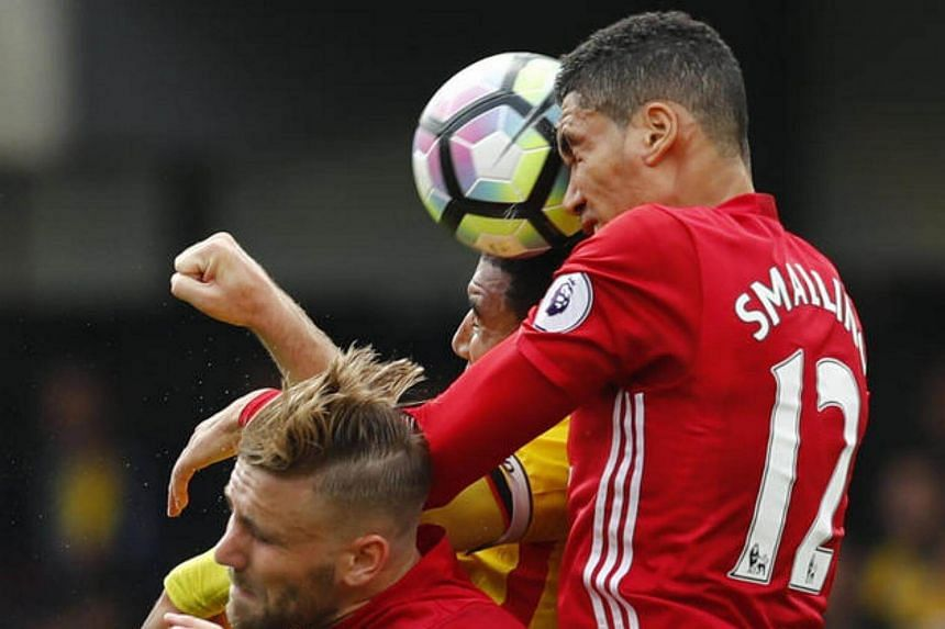 Manchester United's Chris Smalling and Luke Shaw in action with Watford's Troy Deeney.