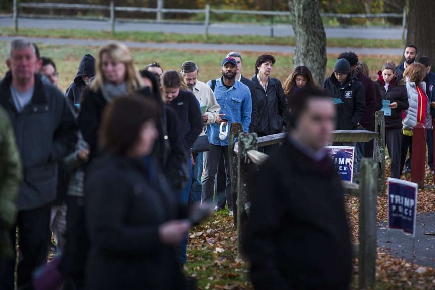 Virginia residents wait in line in the dawn hours to vote in the the 2016 US presidential election before the polls open at an historic property called the 'Hunter House' at Nottoway Park in Vienna, Virginia.