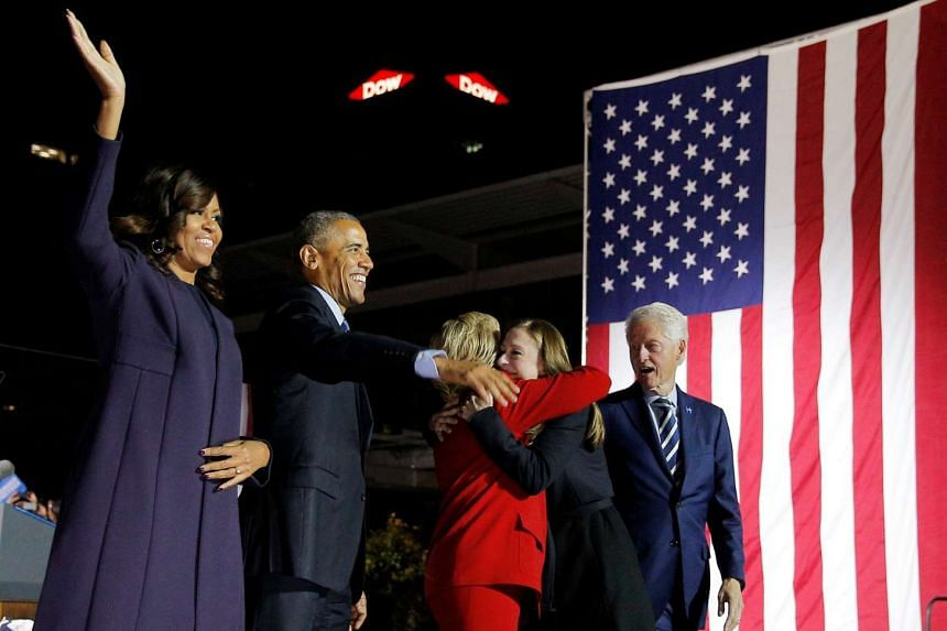 US Democratic presidential nominee Hillary Clinton hugs her daughter Chelsea onstage with former US President Bill Clinton (right), US President Barack Obama (second left) and first lady Michelle Obama (left) at a campaign rally on Independence Mall