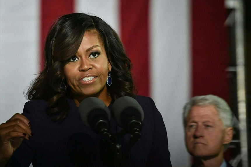 US First Lady Michelle Obama (left) adresses the crowd as US former President Bill Clinton looks on during a rally for Democratic presidential nominee Hillary Clinton, on Independence Mall, on Nov 7, 2016 in Philadelphia, Pennsylvania.
