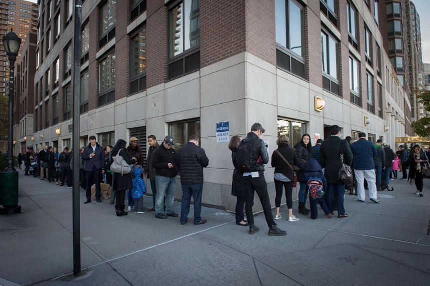People stand in line outside a polling station located at Trump Place in New York on Election Day, Nov 8.