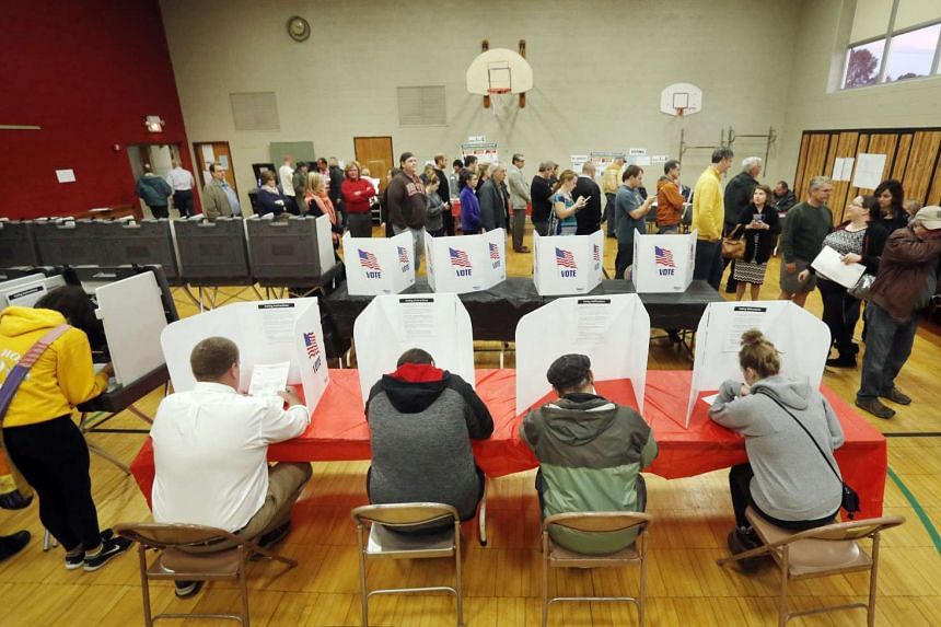 Voters fill out their ballots at a polling location for the 2016 US presidential election at Franklin Elementary School in Kent, Ohio, USA, on Nov 8.