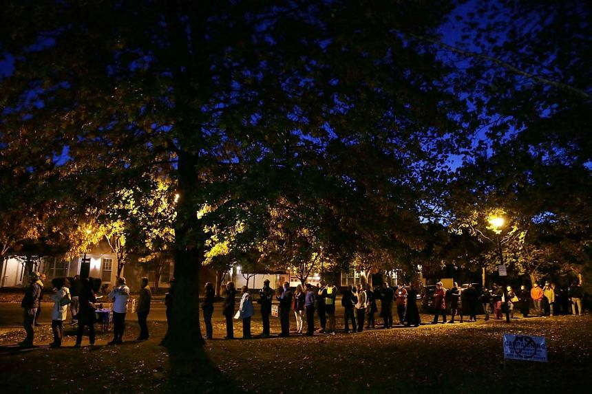 Voters wait in line for casting their ballots outside a polling place on Election Day on Nov 8 in Alexandria, Virginia.