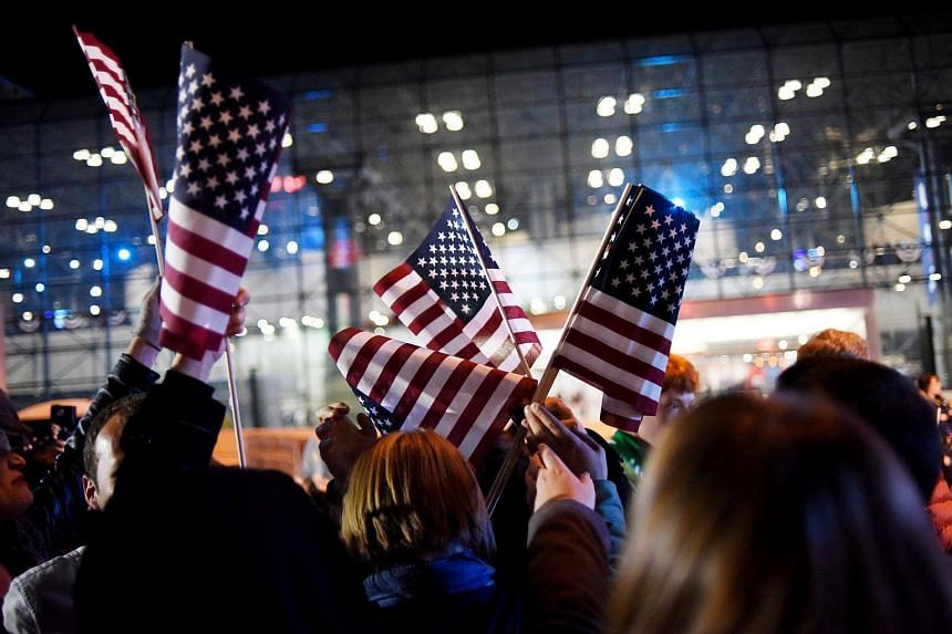 Supporters of US presidential nominee Hillary Clinton grab flags being handed out in the overflow crowd outside the nominee's election night rally at the Jacob K. Javits Convention Centre in New York.