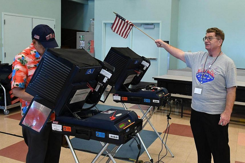 Poll worker Jim Callahan (right) uses an American flag to direct voters to available voting machines at a polling station at John W. Bonner Elementary School.