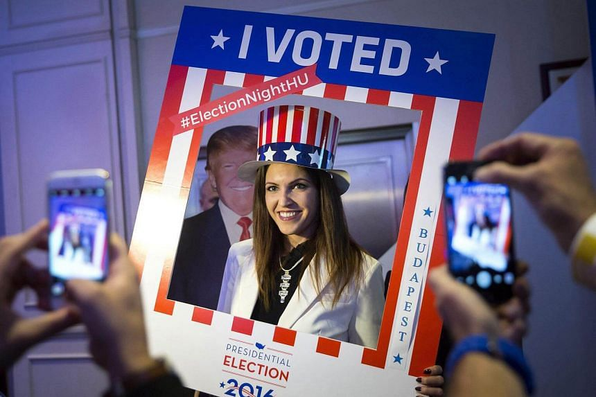 A woman wearing an American top hat poses for a photograph in front of a cardboard figure of Mr Donald Trump.
