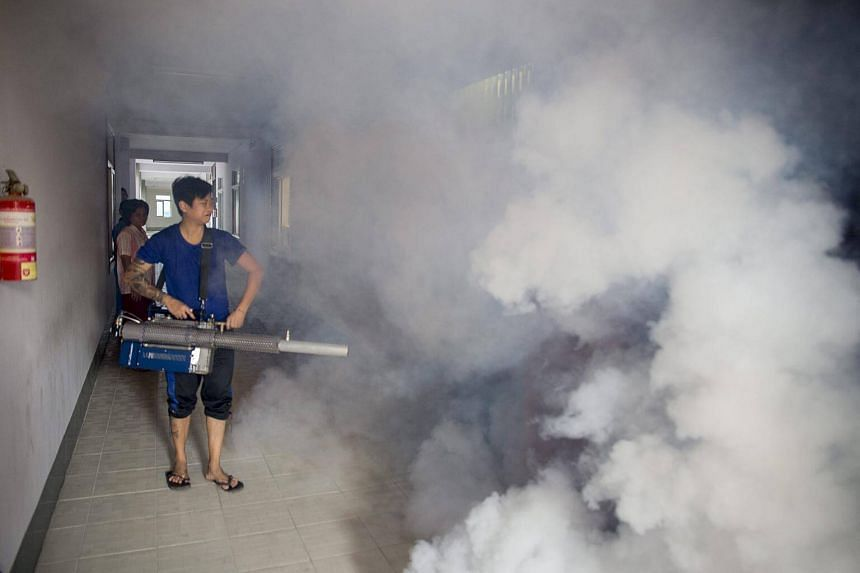 A government health worker sprays chemicals to kill mosquitos at the MyayNu condominium building in Yangon, Myanmar.