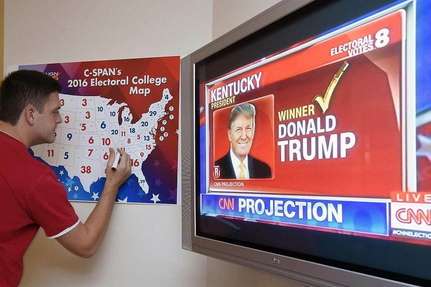 A man colouring in an electoral map as states are projected for Republican presidential candidate Donald Trump or Democratic nominee Hillary Clinton at an election watch party in Coconut Grove, Florida, on Nov 8, 2016.