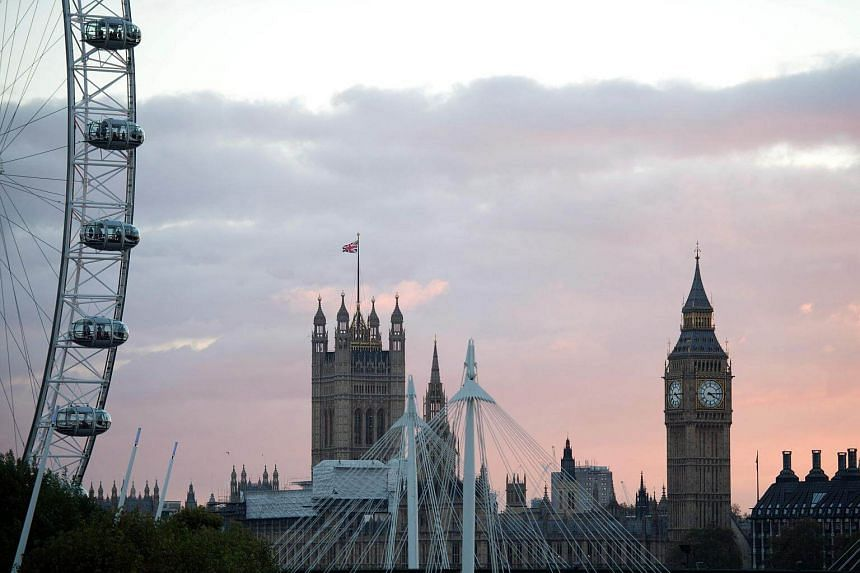 The sun setting beyond the Elizabeth Tower, also known as Big Ben, at the Houses of Parliament (right), and the London Eye, in central London, on Nov 7, 2016.