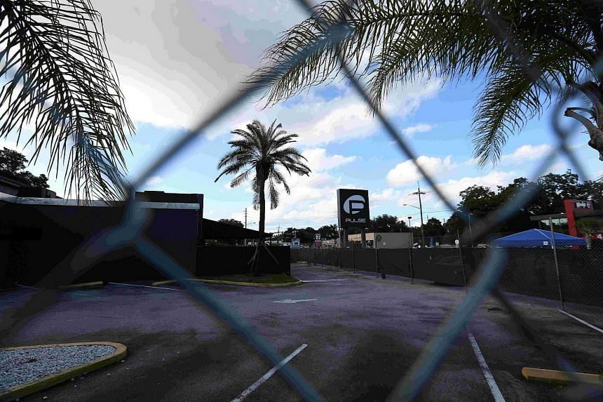 The Pulse night club sign is pictured through a fence following the mass shooting there in Orlando, Florida on June 21, 2016.