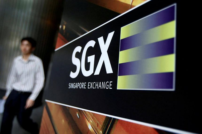 An office worker walks past a logo of the Singapore Stock Exchange outside its premises in Singapore.