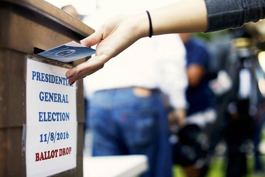 A woman drops her ballot during the presidential election at LA County Registrar Office in Norwalk, California.