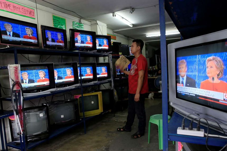 A worker watches the first presidential debate between Hillary Clinton and Donald Trump inside an appliances showroom in Manila on Sept 27, 2016.