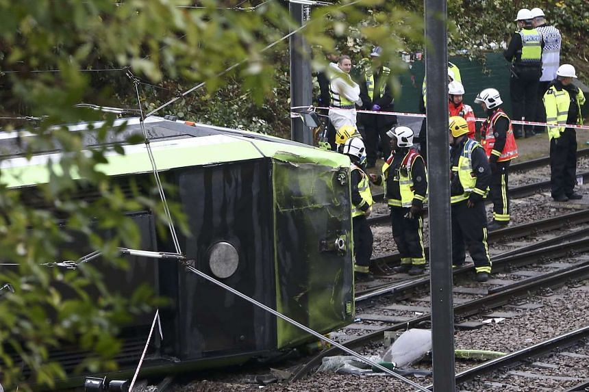 Members of the emergency services work next to a tram after it overturned injuring and trapping some passengers in Croydon, south London on Nov 9, 2016.