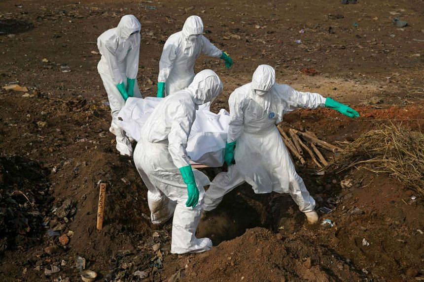 Health workers carry the body of a suspected Ebola victim for burial at a cemetery in Freetown, Sierra Leone, on Dec 21, 2014.
