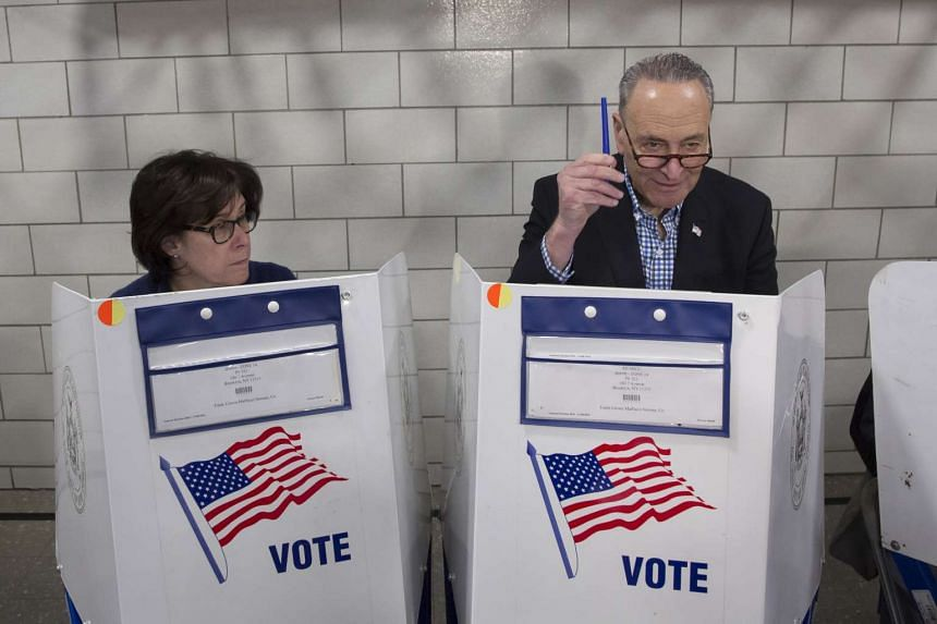 Senator Chuck Schumer, who is up for re-election, holds up his lucky pen while casting his ballot with his wife in New York.