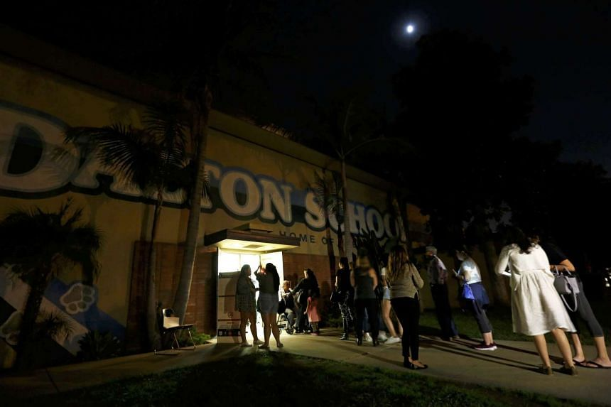 Voters gather outside Dalton Elementary School after the polling station in Azusa, California, was reopened following a shooting in the area.