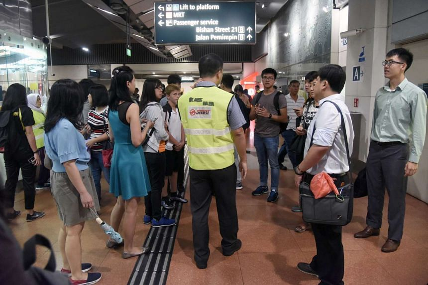 SMRT staff speaking with passengers after a signal fault disrupted services on the Circle Line, on Nov 2, 2016.