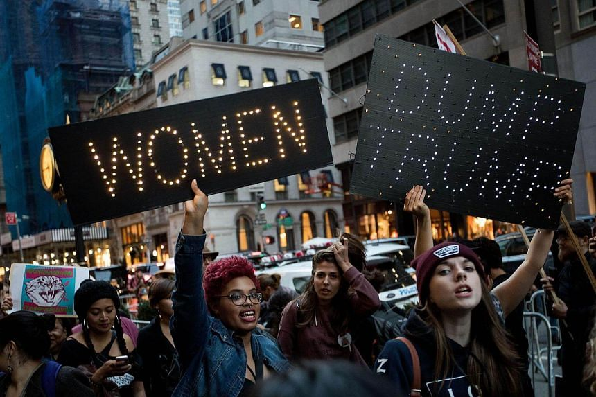 A group of protesters, comprising mostly women, rally against Republican presidential candidate Donald Trump outside Trump Tower on Nov 3, 2016 in New York City.