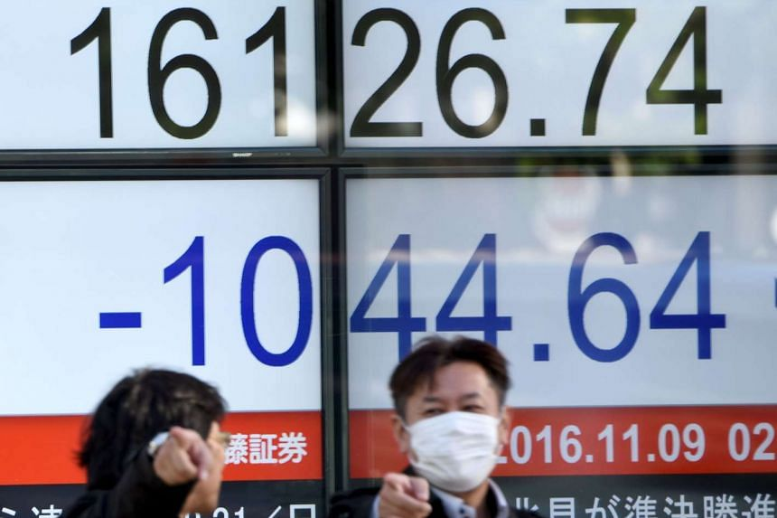 Businessmen talking in front of an electric quotation board flashing the Nikkei key index of the Tokyo Stock Exchange (TSE) in Tokyo on Nov 9, 2016.