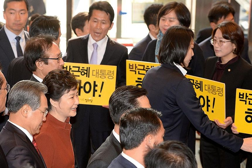 """President Park (in red) walking past lawmakers holding signs telling her to """"step down"""" on her way to meet Speaker of Parliament Mr Chung from the opposition Democratic Party yesterday."""