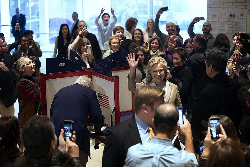 Mrs Clinton after casting her vote, while Mr Clinton (back to camera) marks his ballot slip, yesterday in Chappaqua, New York. A crowd also gathered in New York City at the polling station near Trump Tower, where Mr Trump was due to cast his vote.
