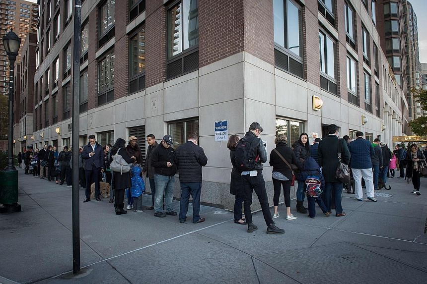 People queueing yesterday outside a polling station at Trump Place in New York, where the voting for the next president of the United States started as early as 6am local time. After an exhausting, bitter and sometimes sordid campaign, Americans fina