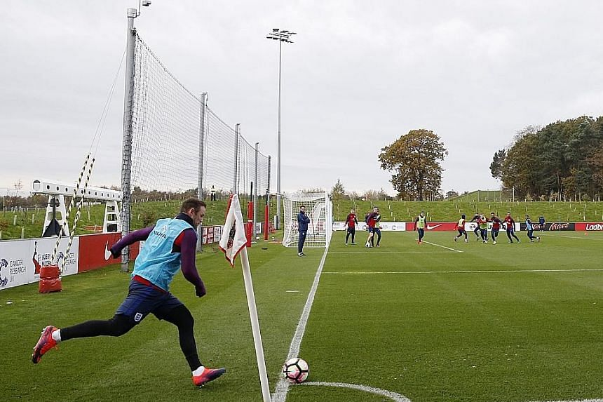 Wayne Rooney and his England team-mates during a training session at St George's Park yesterday. The injured Luke Shaw and Chris Smalling will not line up for England when they take on Scotland on Friday.