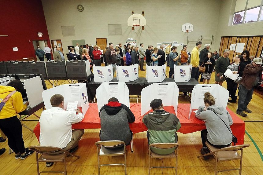 Voters filling out their ballots at a polling location at Franklin Elementary School in Kent, Ohio, yesterday. More than 5,000 police officers were stationed around the United States' largest city yesterday. Security was particularly tight where the