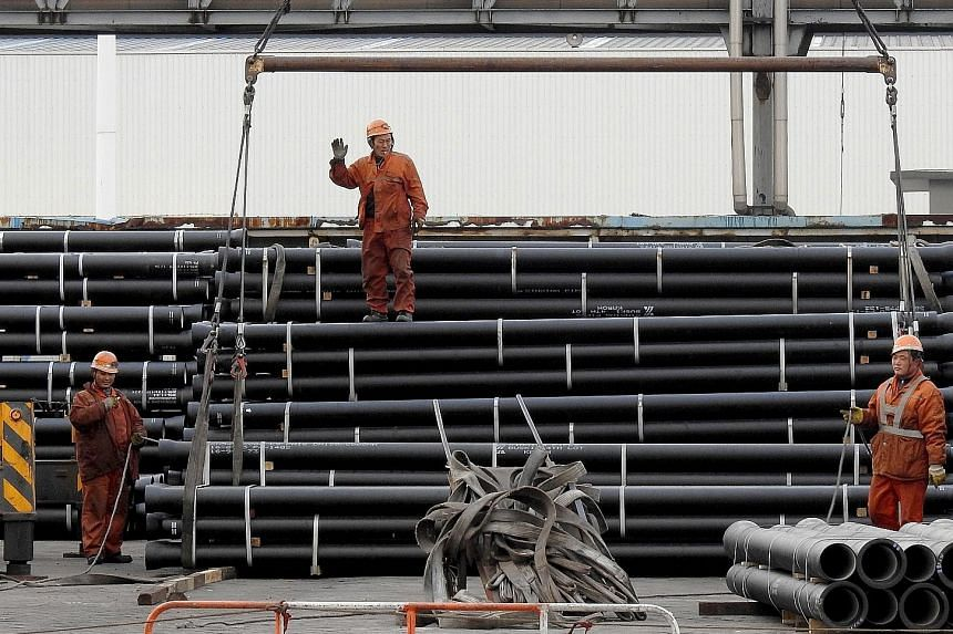 Workers loading steel tubes onto a truck at a logistics centre in Lianyungang in east China's Jiangsu province. Analysts warn that a property boom may be peaking, dampening demand for building materials from cement to steel.