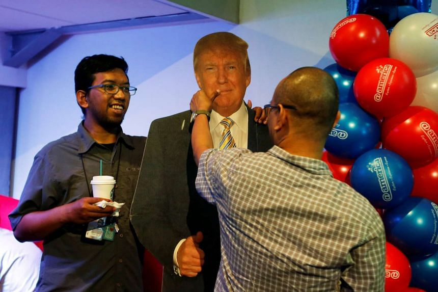 People hold a cardboard cut-out of Donald Trump before taking photos during an elections event at the US embassy's cultural centre in Jakarta, Indonesia, Nov 9, 2016.