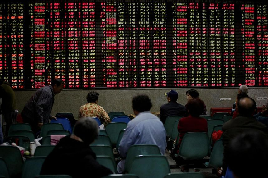 Investors looking at an electronic board showing stock information at a brokerage house in Shanghai, China, on Nov 9, 2016.