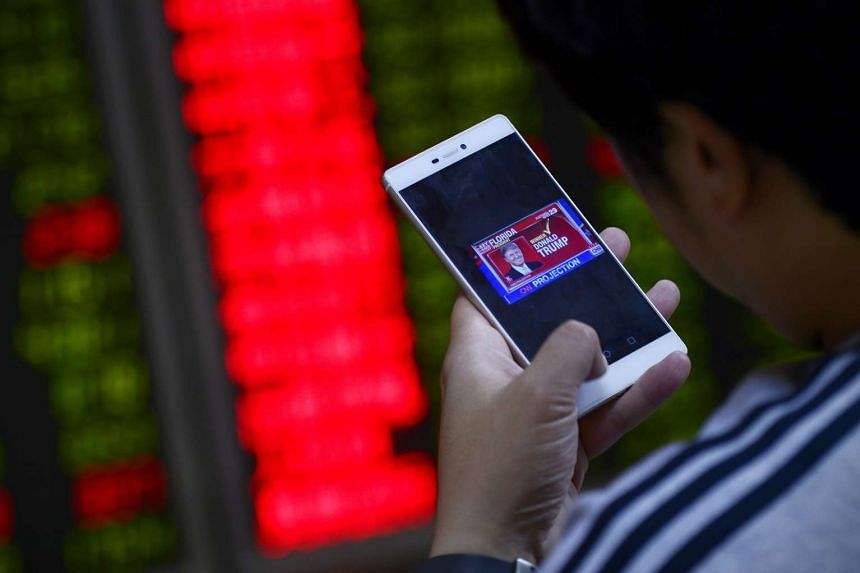 An investor looking at the results of the 2016 US presidential election at a securities company in Beijing on Nov 9, 2016.
