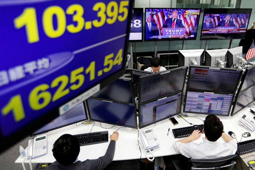 Employees of a foreign exchange trading company working as US president-elect Donald Trump makes a speech on-screen, in Tokyo on Nov 9, 2016.