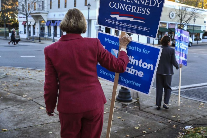 Ms Jody Carlson (left) and her daughter Kim Brenner wear pantsuits and hold signs in support of Hillary Clinton on Election Day in Wellesley, Massachusetts on Nov 8.