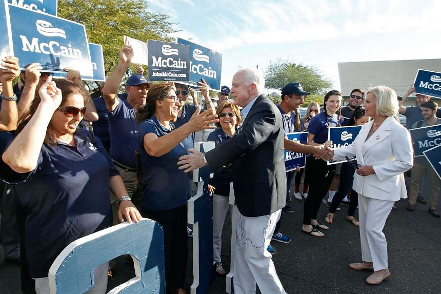 Senator John McCain (centre) and his wife Cindy (right) greeting supporters after casting their votes at the Mountain View Christian Church polling place on Nov 8, 2016 in Phoenix, Arizona.