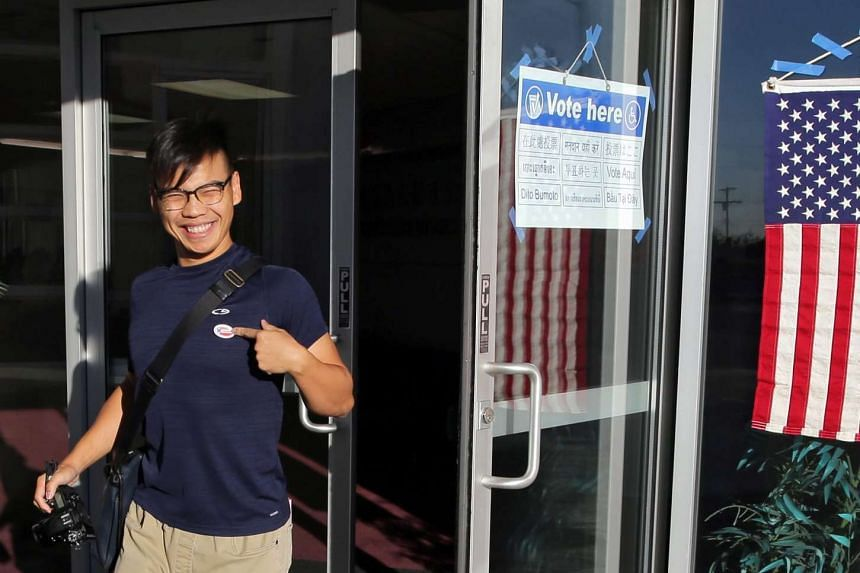 A Chinese-American voter proudly points to his 'I Voted' sticker after voting at the Chinese Evangelical Free Church for the 2016 US presidential election in Monterey Park, California, on November 8.