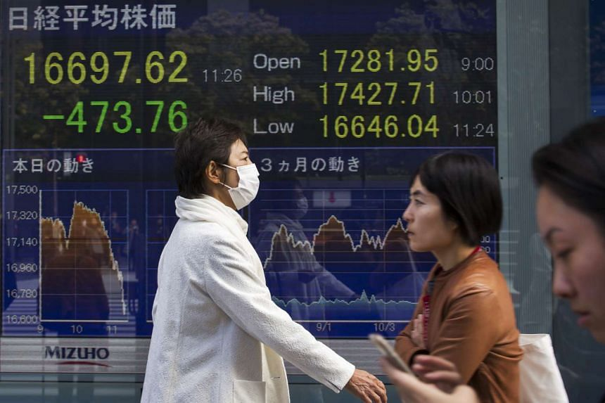 Pedestrians walk past an electronic stock board displaying a figure of the Nikkei Stock Average outside a securities firm in Tokyo, Japan on Nov 9, 2016.