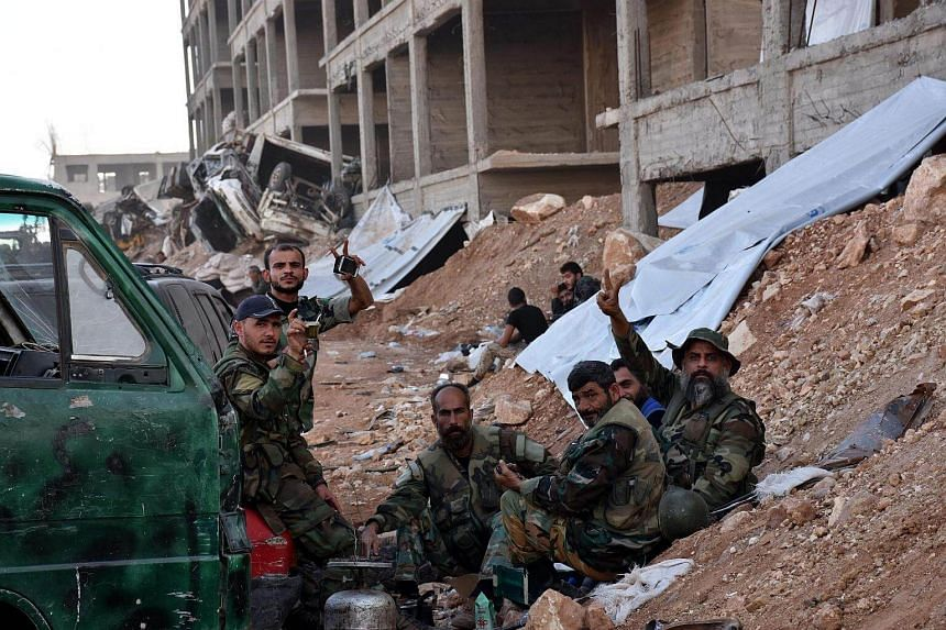 Syrian soldiers take a rest with their lunch after liberating the area of 1070 apartment in Aleppo province, Syria on Nov 8, 2016.