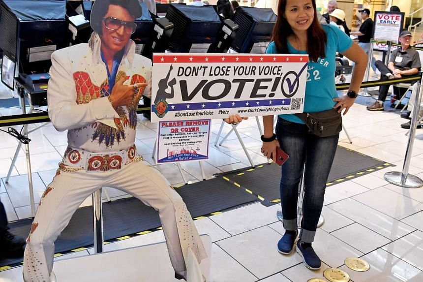First-time voter Jeanne Marquez of Nevada poses next to an Elvis Presley-like cardboard cutout at the Meadows Mall in Las Vegas, Nevada. Voters in Clark County voted early at a record pace in this election ahead of the November 8 general election.